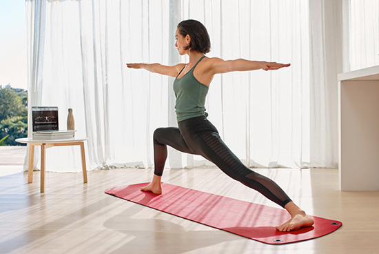 A woman in stands in warrior pose on a yoga mat.