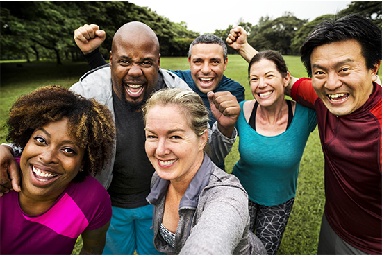 A group of people in workout attire hug and smile.